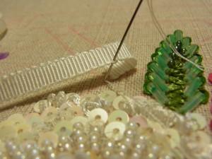 左に倒したリボンを止めます。針は、糸が出ているすぐ側に落とします。