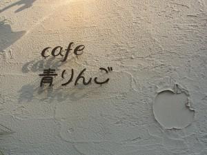 cafe 青りんごの看板です。りんごの模様が壁に付いています。