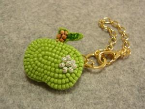 小さい青りんごチャームです。右端にビーズで作ったお花があります。