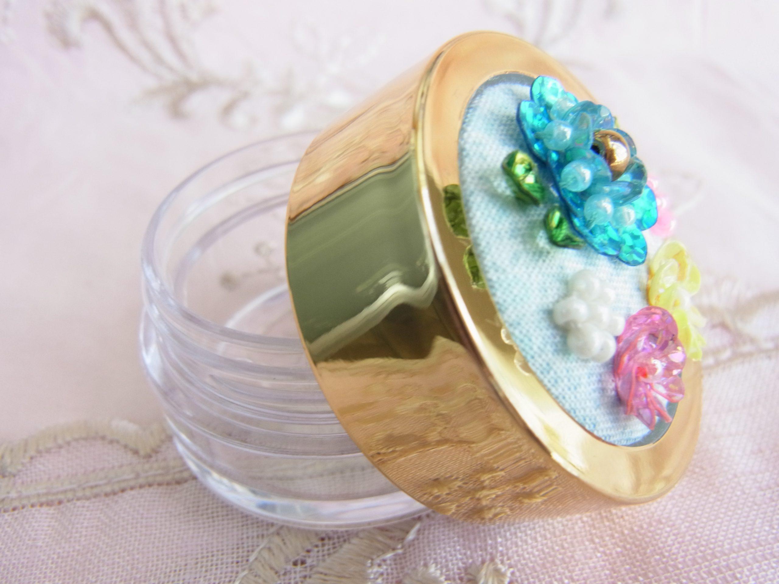 ピアスやサプリメントを入れるのに最適サイズ。ピンク、黄色、ブルーのスパンコールとビーズで刺した花があります。