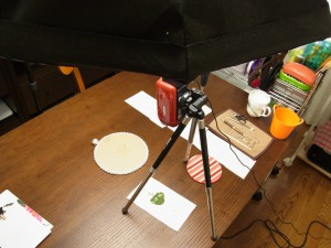 YouTubeにアップする撮影です。大きなライトとビデオがあり、ビーズ刺繍をした生地があります。