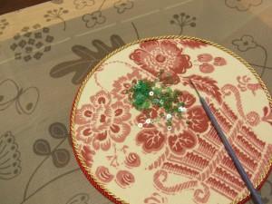 円形の入れ物の上に、スパンコールと針が置いてあります。