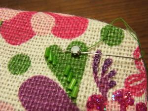ハート型の円形になっている部分に、爪付きのストーンを十字に刺します(2回糸を通します)。