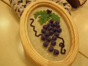 葉がついた一房の葡萄です。木製の楕円形の額にはいっています。