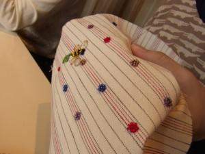 蜂の周りに色とりどりのビーズを使って、小花を作っています。