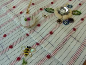 ストライプの生地に刺しています。ふっくらした花びらと小花と蜂が刺してあります。円形のストラップも完成しています。