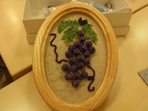 葉がついた葡萄です。木製の楕円形の額に入っています。
