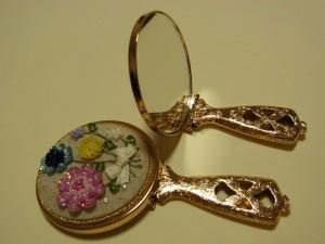 手のひらサイズの折りたたみミラーです。鏡に背中側に、ビーズ刺繍をした生地を貼り付けています。