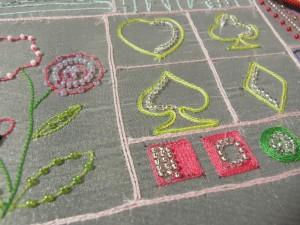 糸刺繍がしてあります。お花やハート、スペード、ダイヤ、クローバー、正方形などが刺してあります。