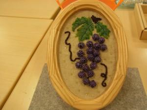 葉付きの葡萄です。木製の楕円形の額に入っています。
