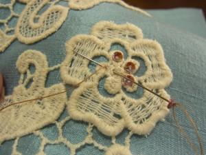 お花の部分にスパンコールを刺しています。スパンコールをすくって、糸がでている位置に針を戻します。