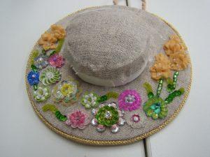 帽子型の土台に、たくさんの花が刺してあります。リボンを使った縦長の花が両脇にあります。