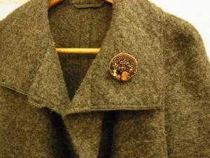 コートの襟元にシックな感じの手作りブローチがあります。