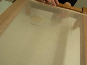 生地をたこ糸で木枠に片側を固定しています。