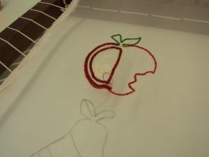 かじられたリンゴにチュールをアップリケして、全体をビーズで刺し埋めます。