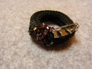 コードで大小の輪を組み合わせて土台を作り、ブローチの金具を縫い止めます。