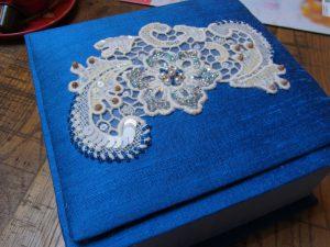 蓋部分に刺繍が終わった花模様の綿ブレイドが飾ってあります。スパンコールとビーズがキラキラしています。