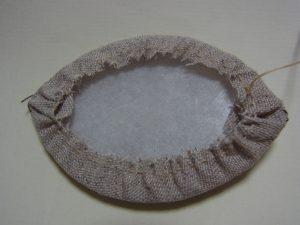 生地にプレートを入れて周りを縫った糸で生地を縮めます。