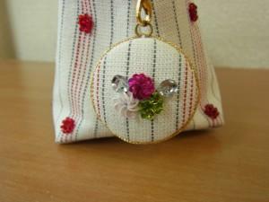ファスナーの持ち手につけた飾りは、包みボタンで作りました。可愛い小花が刺してあります。