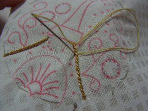 紐を糸で縫い止めています。