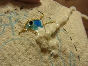 小鳥のお腹の部分は、モールを糸で縫い止めます。