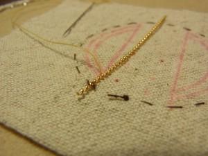 図案線よりワイヤーを少しずらして、生地の裏側から針を出します。