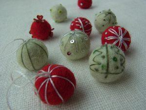 羊毛玉にビーズやスパンコールを刺しています。クリスマスツリーも模様もあります。
