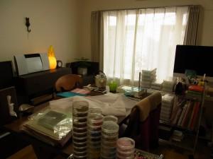 いつも仕事をしている部屋です。大きな出窓の前にテーブルがあり、その上に生地や資料ケース、ビニールなどが沢山あります。