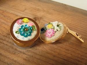 直径4cmほどのアクリルケースと折りたたみの手鏡があります。スパンコールとビーズで刺したお花があります。