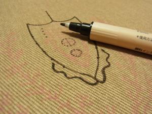 生地に、布描き用マーカーで手書きします。エンブレムのようなデザインです。