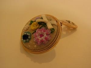 手に平に収まるくらいの手鏡です。スパンコールとビーズのお花が刺してあります。