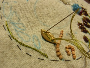 メタルの葉を糸で縫い止めています。