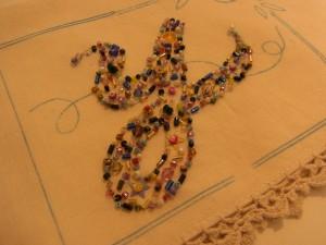 周囲にレースが付いている生地に、イニシャルyをビーズ刺繍しています。