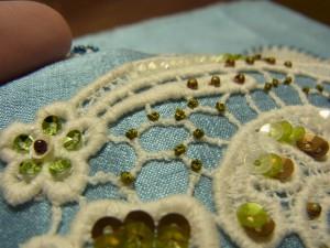 綿ブレイドの網目模様の上に、糸を巻いたおへその形の刺繍があります。