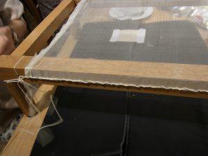たこ糸で木枠に張った生地を固定していきます。