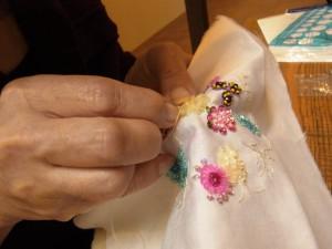 オーガンジーリボンで円形のフリルのお花を作っています。