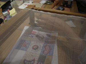 木枠に生地を張り、たこ糸で固定しています。