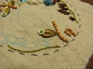 ウッドビーズでさした茎の横に、メタルの葉が刺してあります。葉の先端に花形スパンコールが飾ってあります。