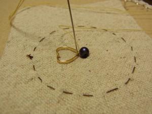 ハート型パーツのとがっている部分を糸で止めています。