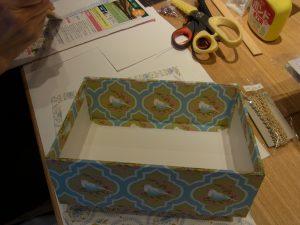 箱を作っています。組み立てたボードに生地を貼っています。