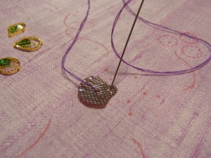 スパンコールに2個穴が空いているので、外側から針を出し内側へ入れます。