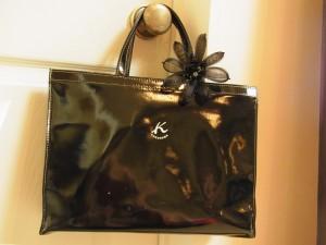 横長のバックの持ち手部分に、透け感のあるコサージュを飾っています。