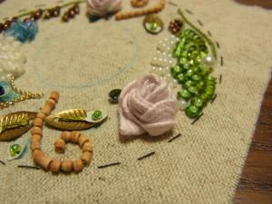 ヒモ状で作った花を生地に縫い止めます。