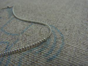 馬の図案線にワイヤーを置いて糸を掛け固定しています。