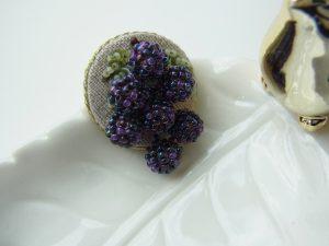 円形のブローチです。小さな葡萄の房が飾ってあります。