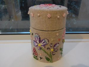 古い茶筒にビーズ刺繍した生地を貼っています。花と蝶々が刺してあります。