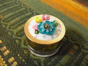 直径4cmのケースの蓋にビーズ刺繍をしています。大小の立体の花が刺してあります。