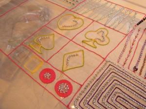アリワークで刺してあります。線状に刺してある部分と円やハート、スペード、ダイヤ、クローバーがあります。