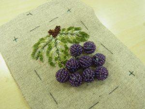葉の下に葡萄の実を縫い止めています。