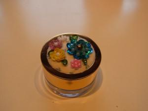 ビーズとスパンコールで刺した3種類の花があります。ケースの蓋に刺した生地がセットしてあります。